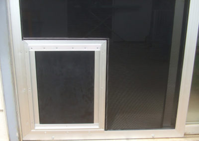 Sliding screen door with pet door.