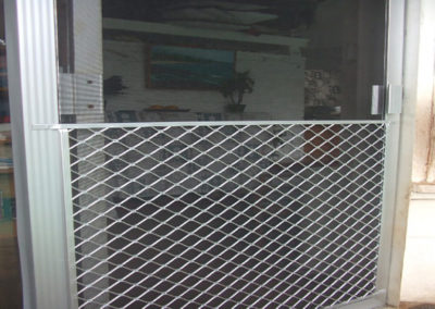 Sliding screen door with pet guard.