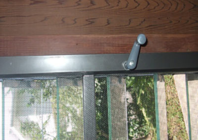 Jalousie handle through screen frame.